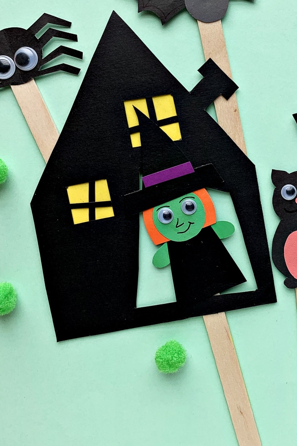 Halloween witch puppet in a paper black house