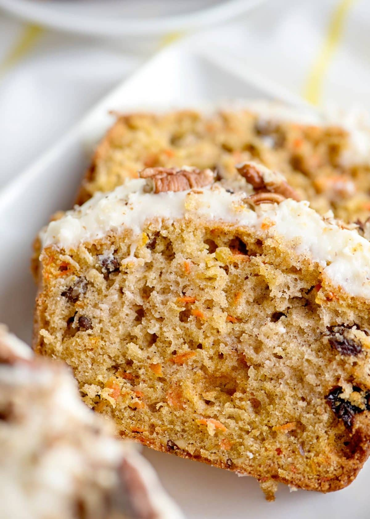 carrot cake bread slices on plate with icing and raisins