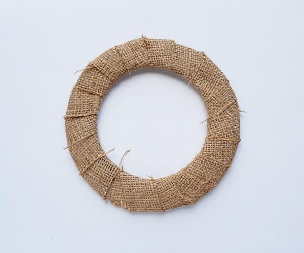 Poinsettia wreath base covered in burlap lace