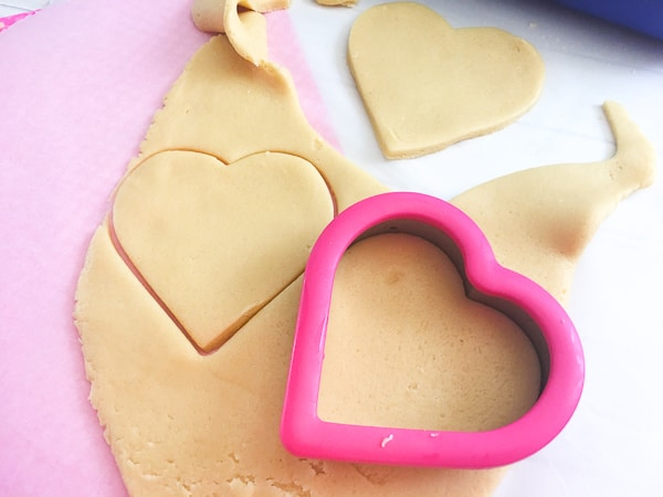 cutting out cookie dough for conversation heart cookies