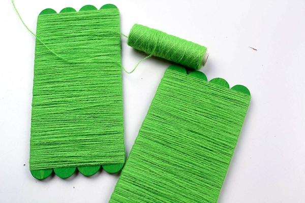popsicle sticks covered with green string to make an elf craft