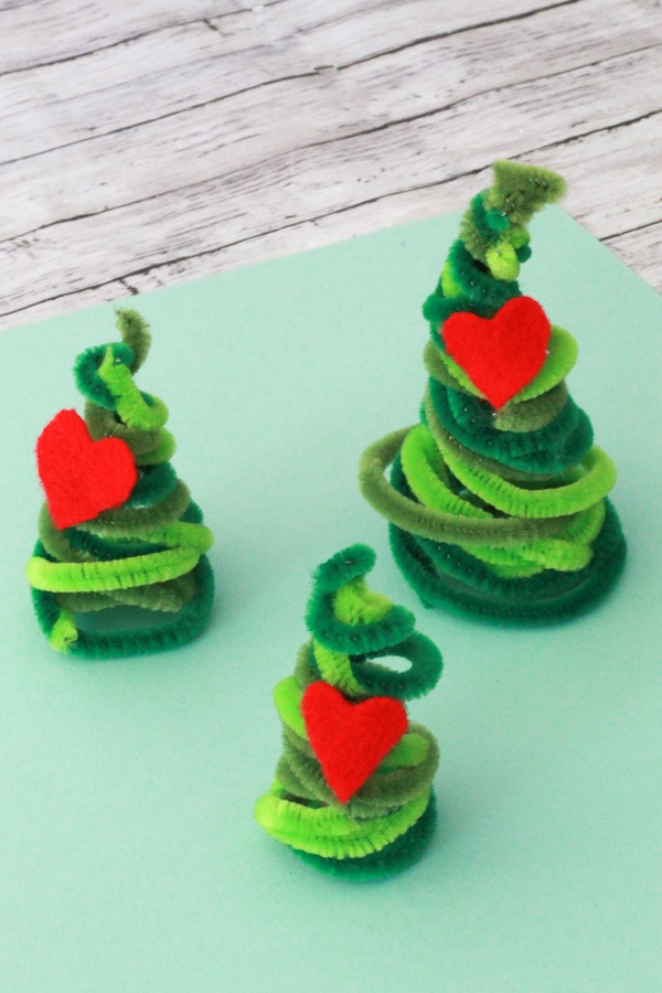 Grinch pipe cleaner christmas trees with red hearts on them.