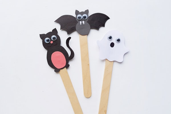 halloween puppets including a paper cat, paper bat and paper ghost on Popsicle sticks
