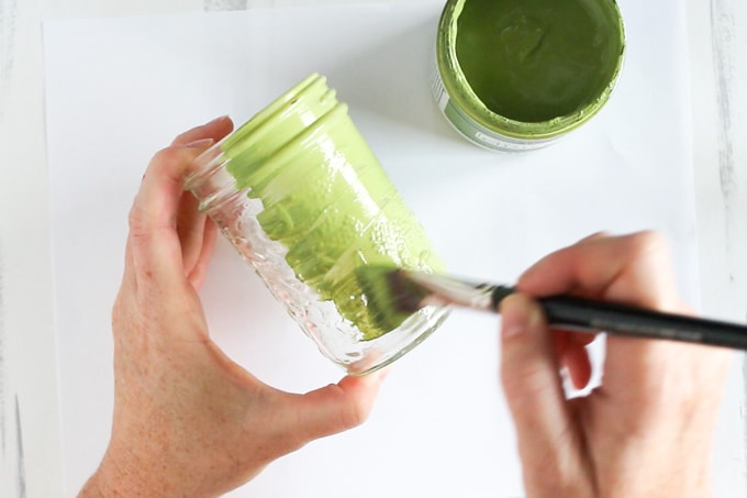 Painting a mason jar green to decorate as a christmas gift
