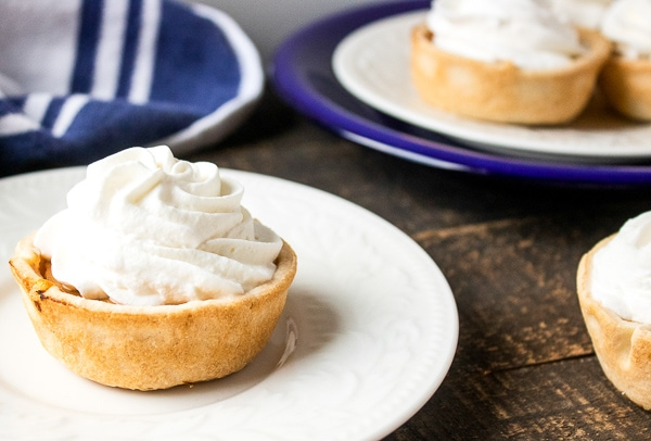 Mini pumpkin pies served on a plate topped with whipped cream