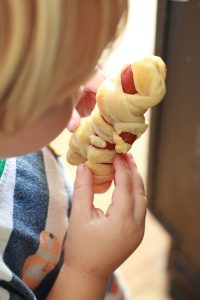 young child holding mummy hot dogs for halloween