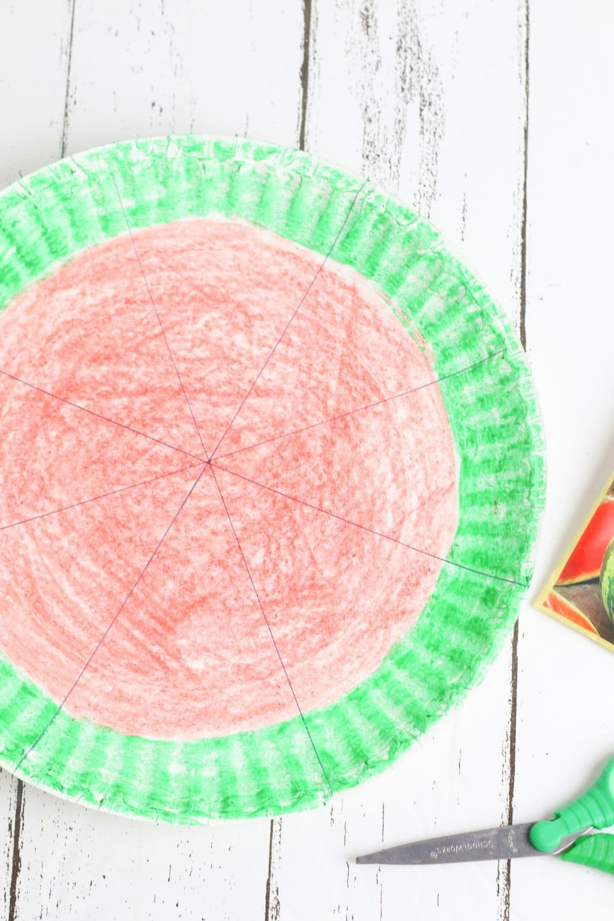paper plate colored like a watermelon, being cut into slilces