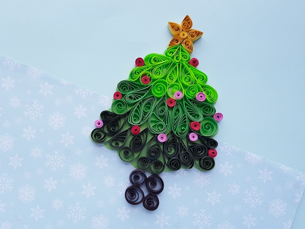A paper quilled christmas tree on blue paper