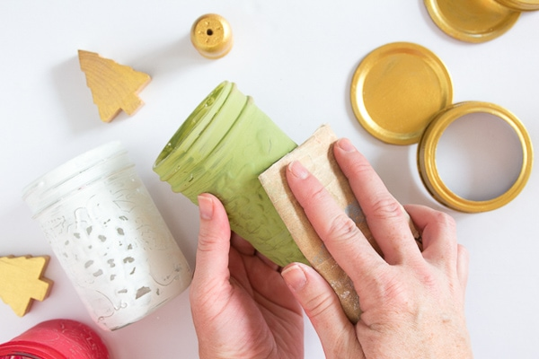 Sanding the mason jars down with sandpaper